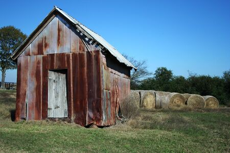 A photo of an old rusty shed next to bales of hay. Stock Photo