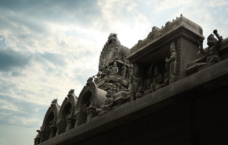 Hindu temple tower with carving of incarnations of lord vishnu seen in a cloudy day