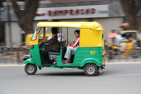 panning shot: Giovane ragazzo che cattura un giro in auto Rikshaw nella citt� di Bangalore Editoriali