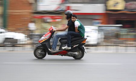 Two Youngsters making a dash on their scooter in bangalore city