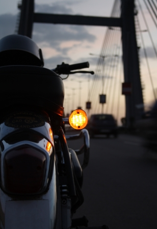 enfield: Details of a motorcycle parked on roadside evening sky behind Stock Photo