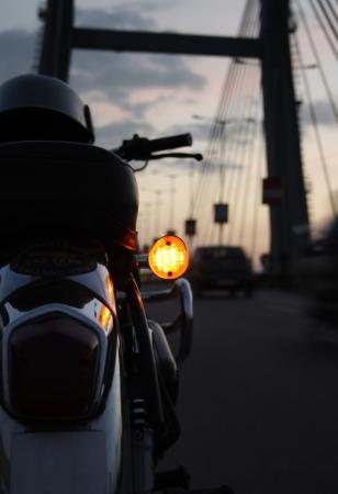 enfield: Dettagli di una moto parcheggiata sul ciglio della strada cielo serale dietro