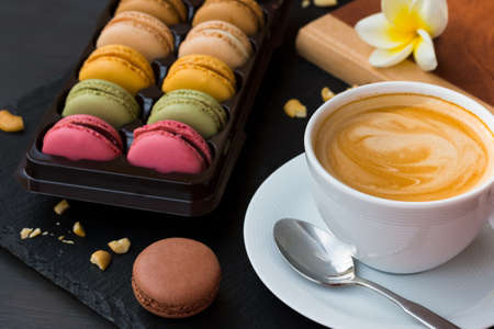French macarons on black stone background. Good morning with a cup of your tasty coffee and favorite book. Stock Photo