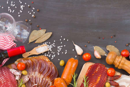 Cutting board with jamon, prosciutto, bacon, salami, chorizo and red wine on dark wooden background. From top view. Archivio Fotografico