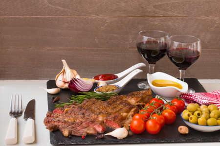 Appetizing grilled meat. Grilled beef entrecote medium roast on a black stone board, red wine and two full wine glasses. Best dinner. Archivio Fotografico