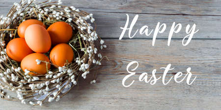Nest with Easter eggs on light gray wooden background. Happy Easter. Elements for table holiday decorating.