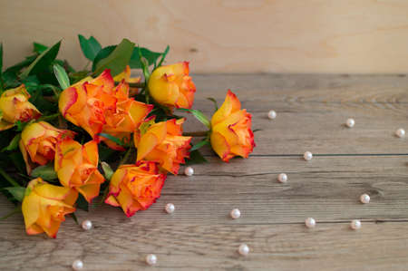 Bouquet of orange roses on a wooden background and scattered beads of pearls. The best present on holiday. Archivio Fotografico