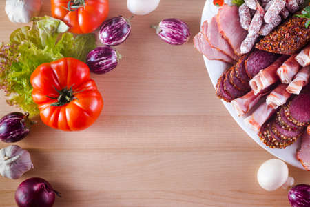 Frame of different appetizer on a plate like jamon, bacon, salami with different vegetables. Archivio Fotografico