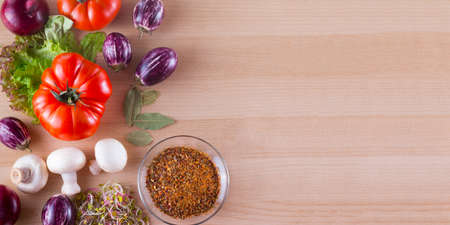 Different vegetables like tomato, eggplants, onions, salad and spices on a wooden background. Archivio Fotografico