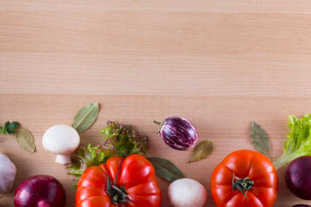 Bordure of different vegetables like tomato, eggplants, onions, salad and spices on a wooden background.