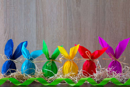 Bordure of Easter eggs in the form of rabbit on a light brown background with green ribbon . Holiday decorating.