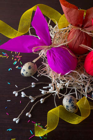 Three Easter eggs in the form of rabbit in the nest with willow branch, yellow ribbon and quail eggs.
