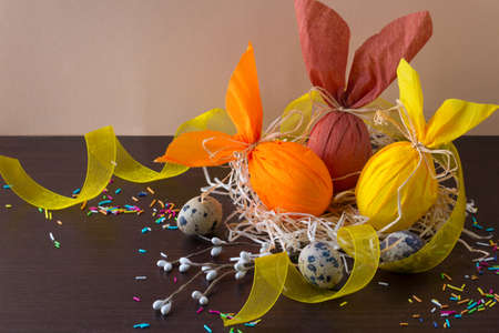 Easter eggs in the form of rabbit in the nest with willow branch, yellow ribbon and quail eggs. Archivio Fotografico