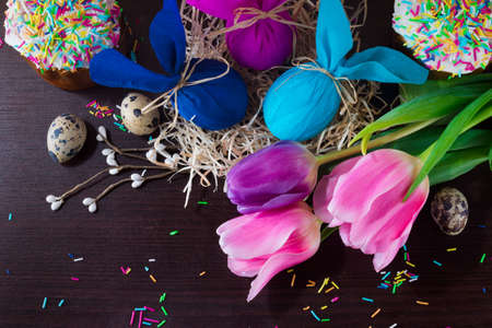 Easter decorating. Easter eggs in the form of rabbit in the nest on a brown wooden background.