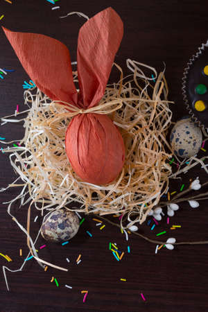Brown Easter egg in form of rabbit in the nest with willow branch and quail eggs. Archivio Fotografico