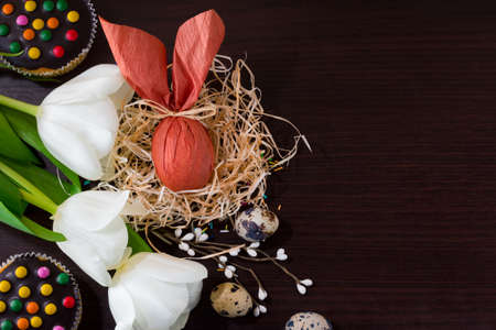 Brown Easter egg in form of rabbit in the nest with willow branches, white tulips, cupcakes and quail eggs.