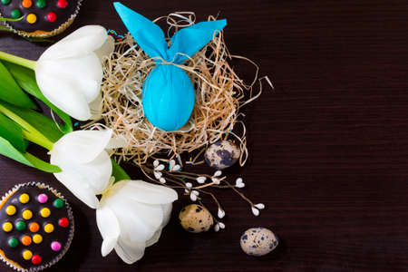 Blue Easter egg in form of rabbit in the nest with willow branches, white tulips, cupcakes and quail eggs. Archivio Fotografico
