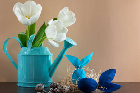 Blue watering can with white tulips and two Easter eggs in the form of rabbit on brown background. Holiday decorating. Archivio Fotografico