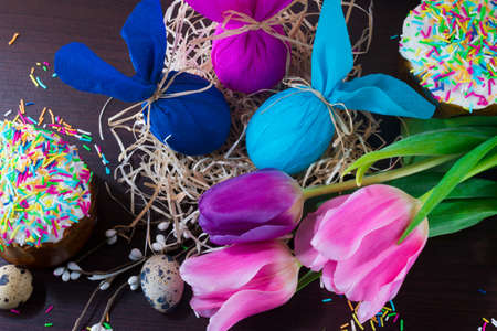 Easter decorating. Easter eggs in the form of rabbit in the nest with willow branch, tulips and easter cakes. Archivio Fotografico