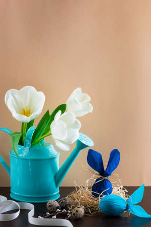 Blue watering can with white tulips and two blue Easter eggs in the form of rabbit on brown background.