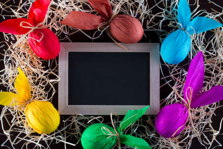 Frame of Easter eggs in the form of rabbit with blackboard to write the text. Holiday decorating. Archivio Fotografico