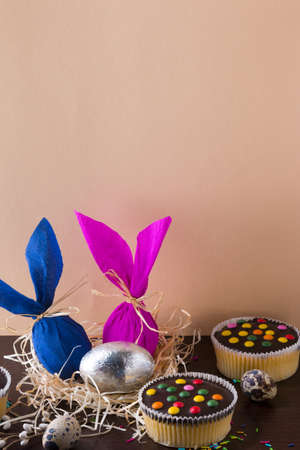 Easter eggs in the form of rabbit on light brown background with cupcakes.