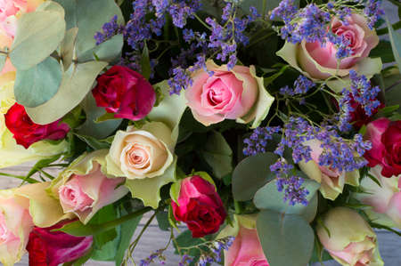 Bouquet of pink and white roses with a branches of eucalyptus. Flowering background