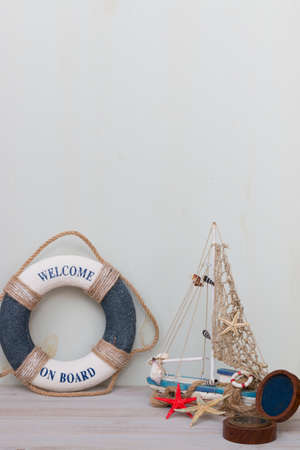 Copy space of set of lifebuoy, boat, compass, starfish on a light gray background. Vacation on the sea.