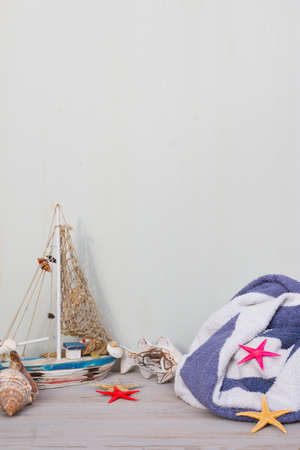 Miniature boat, starfish and seashells stand on a gray background. Towel in white and blue lines. Marine lifetime.