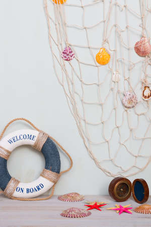 Copy space of set of lifebuoy, compass, starfish on a light gray background. Vacation on the sea.
