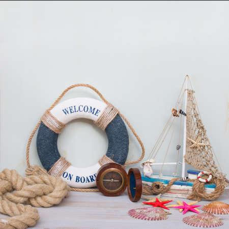 Marine life with starfish, boat, compass and seashells. Copy space on light background, retro toned.
