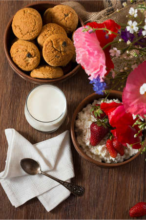 Tasty breakfast of homemade cottage cheese with strawberry, glass of milk and cookies