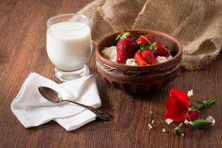 Tasty village breakfast of homemade cottage cheese with strawberry, glass of milk with bunch of poppy flower