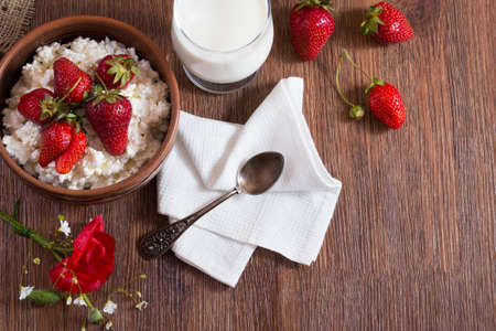 Village breakfast of homemade cottage cheese with strawberry, glass of milk with bunch of poppy flower