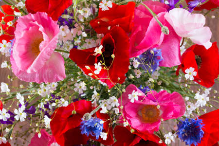 Bouquet of red and pink poppy and blue cornflower top view. Flowers background