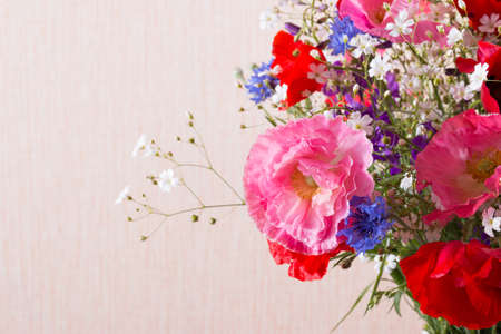 Bouquet of red and pink poppy and blue cornflower on light background. Summer flowers background.
