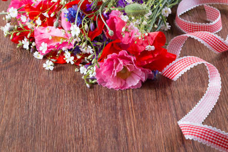 Bouquet of red and pink poppy and blue cornflower ley on brown wooden background.
