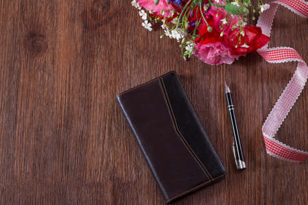 Notebook and pen lay on a brown wooden background. Bunch of poppy flower and cornflower Archivio Fotografico