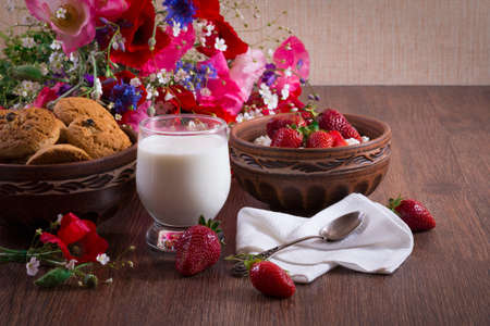 Breakfast of homemade cottage cheese with strawberry, glass of milk and bunch of poppy flower. Romantic mood. Archivio Fotografico