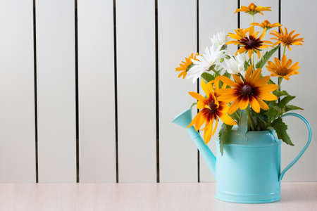 Yellow Rudbeckia , coneflowers, black-eyed-susans, flowers and other sumer flowers in a blue watering can.