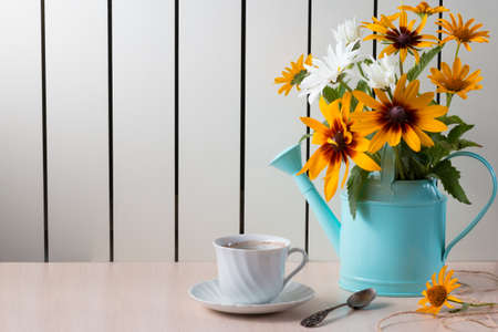 Bouquet of summer flowers like heliopsis, chamomile, rudbeckia and gaillardia in watering can.