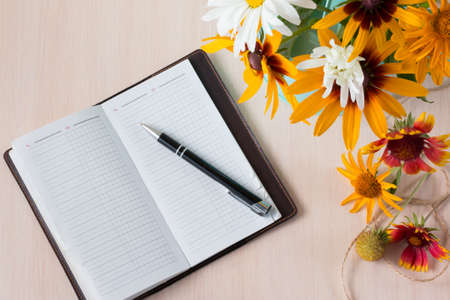 Bouquet of summer flowers like heliopsis, chamomile, rudbeckia and gaillardia with notebook and pen. Top view.