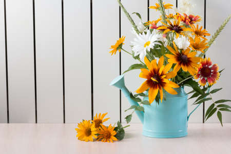 Bouquet of summer flowers like heliopsis, chamomile, rudbeckia and gaillardia in blue watering can on the light background.