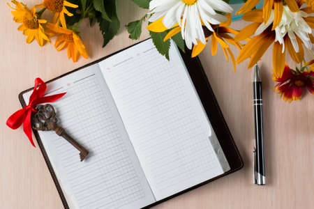 Summer flowers like heliopsis, chamomile, rudbeckia and gaillardia with notebook, old key and pen. Top view.