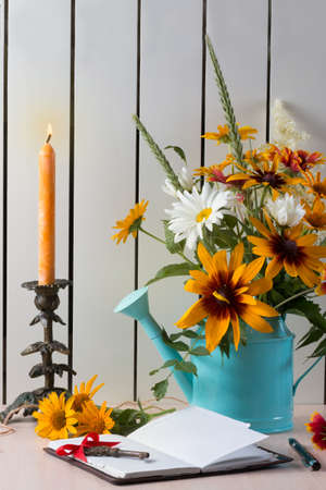 Orange summer flowers like heliopsis, chamomile, rudbeckia and gaillardia with notebook, old key and pen. Candlestick and orange candle.