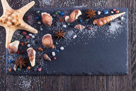 Food art idea for kids breakfast or dessert. Chocolate candies in the form of seafood on black background Archivio Fotografico