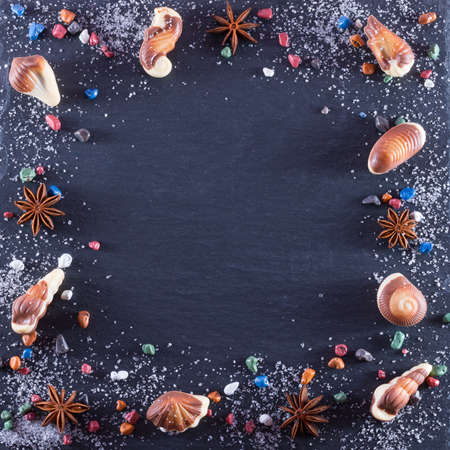 Frame of candy in form of seafood with chocolate stones, sugar and anice. Marine topic on black stone Archivio Fotografico