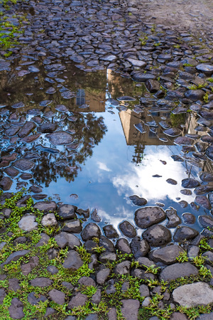 Reflections of buildings and blue sky over puddle after rain photo