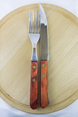 Fork and knife with red wooden handle on a plate of natural wood  Reklamní fotografie