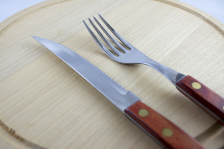 grunge silverware: Fork and knife with red wooden handle on a plate of natural wood  Stock Photo